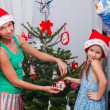Young mother and her adorable little girl in Santa Claus hats decorate their Christmas tree — Stock Photo #32210393
