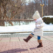 Little cute girl walks in the winter on a sunny day outdoors — Stock Photo #32210591