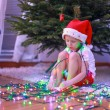 Little beautiful girl in Santa Claus hat sitting under the Christmas tree among garlands — Stock Photo
