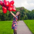 Young nice girl in beautiful dress with red balloons have fun outdoor — Stok fotoğraf