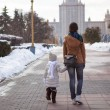 Young mother and her adorable little daughter walking on a sunny winter day — Stock Photo