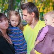 Portrait of Young charming family with two kida enjoying the weather in yellow autumn park — Foto de Stock