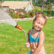 Adorable happy little girl pouring water from a hose and laughing — Stock Photo