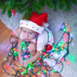 Little beautiful girl in Santa Claus hat sitting under the Christmas tree among garlands — Stock Photo #32211837