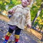Portrait of Little beautiful girl walking alone in autumn park — Stock Photo #32212077