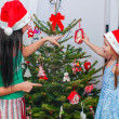 Young mother and her adorable little girl in Santa Claus hats decorate their Christmas tree — Foto Stock