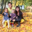 Young mother and father with their two little daughters enjoying the weather in yellow autumn park — Stock Photo #32212143