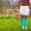 Young woman in rubber boots holding the straw basket with red apples at autumn time — Stock Photo