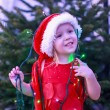 Little beautiful girl in a red dress and hat with Christmas garlands around her neck — Stock Photo #32212263