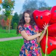 Close-up of Young attractive woman in beautiful dress with red balloons — Stock Photo