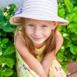 Portrait of cute little girl in hat sitting at the garden — Stock Photo