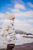 Little cute happy girl is walking in the snow on a sunny winter day — Stock Photo