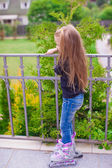 Little cute girl on roller skates in front of her house — Stock Photo