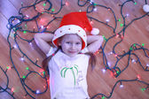 Little happy girl lies among the multi-colored lights on a wooden floor — Stock Photo
