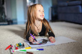 Portrait of a sweet charming young girl who draws with his coloring at home — Stock Photo
