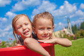 Two cute little happy girls having fun in small pool on the courtyard outdoor and enjoy their vacation — Stock Photo