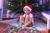 Adorable little girl in chritmas hat sitting under the New Year tree among garlands — Stock Photo