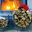 Firewood with Santa Claus hat in the house near a fireplace — Stock Photo