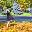 Little funny girl throws autumn leaves in the park on a sunny fall day — Stock Photo #32779667