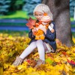 Pretty Fashion girl sitting under a maple tree with doll and red leaf on sunny autumn day — Stock Photo