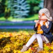 Pretty Fashion girl sits under a maple tree with doll on sunny autumn day — Stock Photo