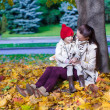 Fashion young mother and her adorable little daughter enjoying a sunny day in autumn park — Stock Photo