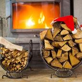 Ved med jultomten hatt i huset nära öppen spis — Stockfoto