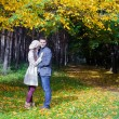 Young couple in love on the big autumn meadow under large maple tree at sunny fall day — Stock Photo