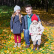 Young father and his two adorable little daughters walking in the autumn park enjoying a sunny day — Stok fotoğraf
