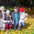 Adorable family of four enjoying a wonderful sunny autumn day in the park — Stock Photo