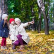 Young mother and her adorable daughter enjoying charming walk in yellow autumn forest on a warm sunny day — Stock Photo