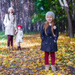 In the foreground is a beautiful sweet girl behind her mother and sister at autumn park — Stock Photo