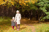 Young mother and her charming beautiful daughter walk in autumn park on a sunny warm day — Stock Photo