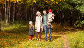 Young parents with their wonderful beautiful daughter walk in autumn park on a sunny warm day — Foto Stock