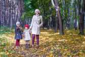 Young mother and her adorable daughters walking in yellow autumn forest on a warm sunny day — Stock Photo