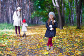 Young mother and her adorable daughter walking in yellow autumn forest on a warm sunny day — Stock Photo