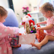 Two charming little sisters early in the morning opening Christmas gifts — Foto de Stock