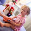 Little adorable girl early in the morning opening Christmas gifts — ストック写真