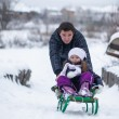 Young father with his baby daughter in a sleigh ride and enjoy sunny winter day — Stock Photo