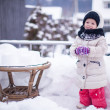 Little funny and cheerful girl having fun in the yard at winter sunny day — Foto Stock