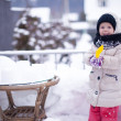 Little funny adorable girl having fun and playing in the yard at winter sunny day — Stockfoto