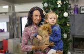 Ung mamma med sin lilla dotter och söt hund inför nyår på julgran — Stockfoto