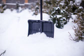 Metal shovel in a large high snowdrift at winter day — Stock Photo