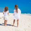Rear view of two little sisters in white clothes having fun at tropical sand beach — Stock Photo #33385237