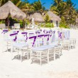 White wedding chairs decorated with purple bows on sandy beach — Stock Photo #33385575
