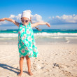 Adorable little girl having fun on an exotic white beach at sunny day — Stock Photo