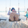 Young mother and her cute daughter swinging on a swing at the beach — Stock Photo #33385781