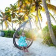 Adorable little girl in a dress and sunglasses on swing at white sandy Caribbean beach — Stock Photo