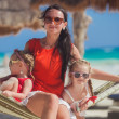 Young mother and her little daughters having rest in a hammock on Caribbean white beach — Stock Photo