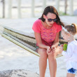 Stock Photo: Mother and daughter on tropical vacation relaxing in hammock